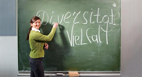 Das Bild zeigt eine Dozentin, die an eine Kreidetafel die Worte